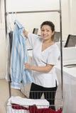 Портрет счастливой рубашки смертной казни через повешение молодой женщины перед стиральными машинами в Laundromat стоковые изображения rf