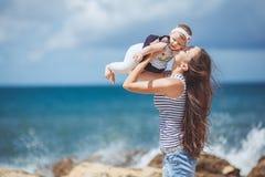 Портрет счастливой семьи женщины и ребенка имея потеху голубым морем в летнем времени Стоковая Фотография