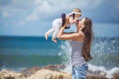 Портрет счастливой семьи женщины и ребенка имея потеху голубым морем в летнем времени Стоковое Изображение
