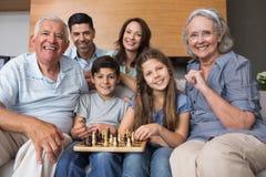 Портрет счастливой семьи из нескольких поколений играя шахмат в живущей комнате стоковое фото rf