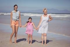 Портрет счастливой семьи мульти-поколения держа руки на пляже Стоковое Фото