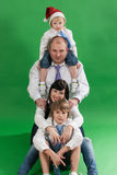 Портрет счастливой семьи при 2 дет сидя на студии на зеленой предпосылке Стоковые Фото