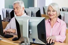 Портрет счастливой старшей женщины используя компьютер в классе Стоковая Фотография