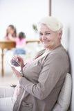 Портрет счастливой старшей женщины используя цифровую таблетку с грифелем дома Стоковое Изображение