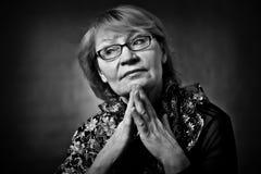 Портрет счастливой старшей женщины ся на камере Над черной предпосылкой стоковые изображения rf