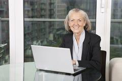 Портрет счастливой старшей коммерсантки при компьтер-книжка сидя на таблице Стоковые Изображения RF