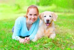 Портрет счастливой усмехаясь женщины предпринимателя и собаки золотого Retriever лежит на лете травы Стоковые Изображения