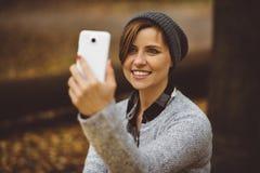 Портрет счастливой, усмехаясь женщины сидя самостоятельно в лесе с smartphone Девушка Millenial играя социальные средства массово Стоковая Фотография
