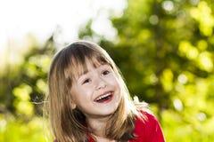 Портрет счастливой усмехаясь маленькой девочки на солнечном мёде травы лета Стоковые Изображения RF
