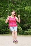 Портрет счастливой усмехаясь молодой девушки женщины среднего возраста в красных футболке и джинсах замыкает накоротко на качании Стоковое Изображение