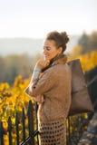 Портрет счастливой элегантной женщины ослабляя в парке осени Стоковая Фотография RF