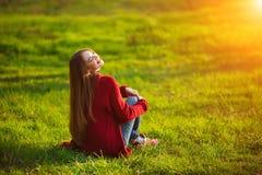 Портрет счастливой sporty женщины ослабляя в парке на зеленом луге Радостная женская модель дышая свежим воздухом outdoors Стоковые Изображения RF