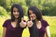 Портрет счастливые сестры дублирует показывать большие пальцы руки вверх Стоковые Фотографии RF
