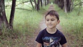 Портрет Счастливый красивый мальчик идет через древесины усмехаясь и наслаждаясь природой в дне лета солнечном сток-видео