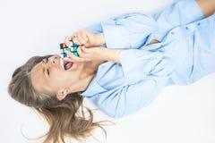 Портрет счастливый усмехаясь белокурый женский играть с кубом Rubik Стоковая Фотография RF