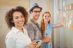 Портрет счастливых бизнесменов готовя стеклянную стену Стоковое фото RF