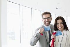 Портрет счастливых бизнесменов показывая удостоверения личности в выставочном центре стоковая фотография