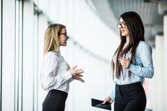 Портрет счастливых бизнес-леди обсуждая совместно в офисе Стоковые Фотографии RF