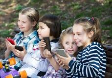 Портрет счастливых детей играя с телефонами Стоковые Изображения
