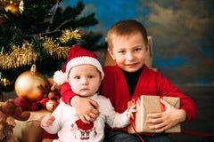 Портрет счастливых детей с подарочными коробками и украшениями рождества 2 дет имея потеху дома Стоковые Фото