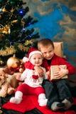 Портрет счастливых детей с подарочными коробками и украшениями рождества 2 дет имея потеху дома Стоковая Фотография