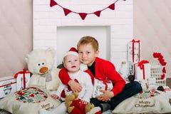 Портрет счастливых детей с подарочными коробками и украшениями рождества 2 дет имея потеху дома Стоковое фото RF