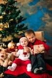 Портрет счастливых детей с подарочными коробками и украшениями рождества 2 дет имея потеху дома Стоковые Фотографии RF