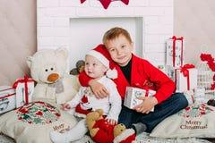 Портрет счастливых детей с подарочными коробками и украшениями рождества 2 дет имея потеху дома Стоковые Изображения