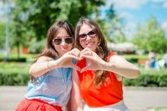 Портрет счастливых молодых городских девушек в европейском городе Кавказские туристы делая сердца их руками в Стоковые Фотографии RF