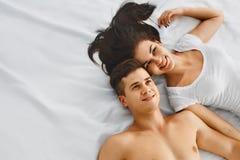 Портрет счастливых молодых пар лежа на кровати совместно стоковые изображения