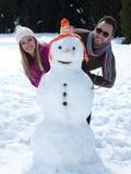 Портрет счастливых молодых пар с снеговиком Стоковое Фото