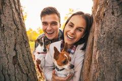 Портрет счастливых пар с собаками outdoors в парке осени стоковое фото