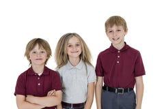 Портрет счастливых ребеят школьного возраста в форме над белой предпосылкой стоковое фото rf
