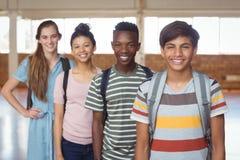 Портрет счастливых студентов стоя с schoolbags в кампусе Стоковая Фотография RF