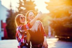 Портрет счастливых 2 усмехаясь девушек делая фото selfie на smartphone предпосылка урбанская Заход солнца вечера над Стоковое Фото