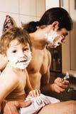 Портрет сына и отца наслаждаясь пока бреющ совместно, концепция людей образа жизни, счастливая семья Стоковые Фото