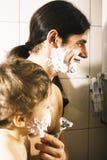 Портрет сына и отца наслаждаясь пока бреющ совместно, концепция людей образа жизни, счастливый крупный план семьи Стоковое Фото