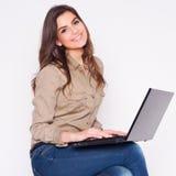 Портрет ся молодой женщины работая на компьтер-книжке пока сидящ на стуле. Стоковая Фотография