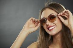 Солнечные очки и усмехаться женщины нося стоковое фото