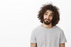 Портрет талии-вверх дружелюбного милого испанского парня с бородой и афро стилем причёсок, нося вскользь striped футболкой Стоковая Фотография