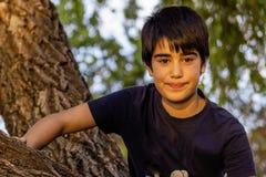 Портрет талии-вверх красивого счастливого усмехаясь молодого мальчика в парке стоковое изображение rf