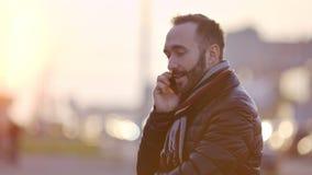 Портрет творческого молодого бородатого мужчины имея потеху усмехаясь и говоря используя смартфон видеоматериал