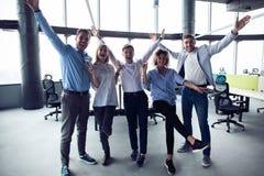 Портрет творческой команды дела стоя совместно и смеясь Multiracial бизнесмены совместно на запуске стоковое изображение rf