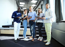 Портрет творческой команды дела стоя совместно и смеясь над Multiracial бизнесмены совместно на запуске Стоковые Изображения