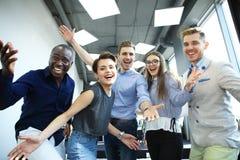 Портрет творческой команды дела стоя совместно и смеясь над Multiracial бизнесмены совместно на запуске Стоковое Изображение