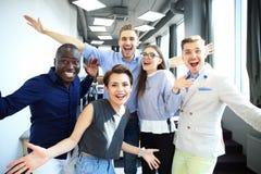Портрет творческой команды дела стоя совместно и смеясь над Multiracial бизнесмены совместно на запуске Стоковые Изображения RF