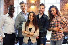 Портрет творческой команды дела стоя совместно и смеясь над Multiracial бизнесмены совместно на запуске Стоковые Фотографии RF