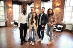 Портрет творческой команды дела стоя совместно и смеясь над Multiracial бизнесмены совместно на запуске Стоковое фото RF
