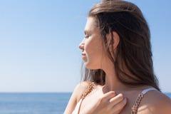 Портрет темн-с волосами женского человека против моря стоковая фотография rf