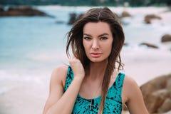 Портрет темн-с волосами, suntanned девушки в ярком купальнике, отдыхая на лазурном береге, имеет выразительную сторону стоковое изображение rf